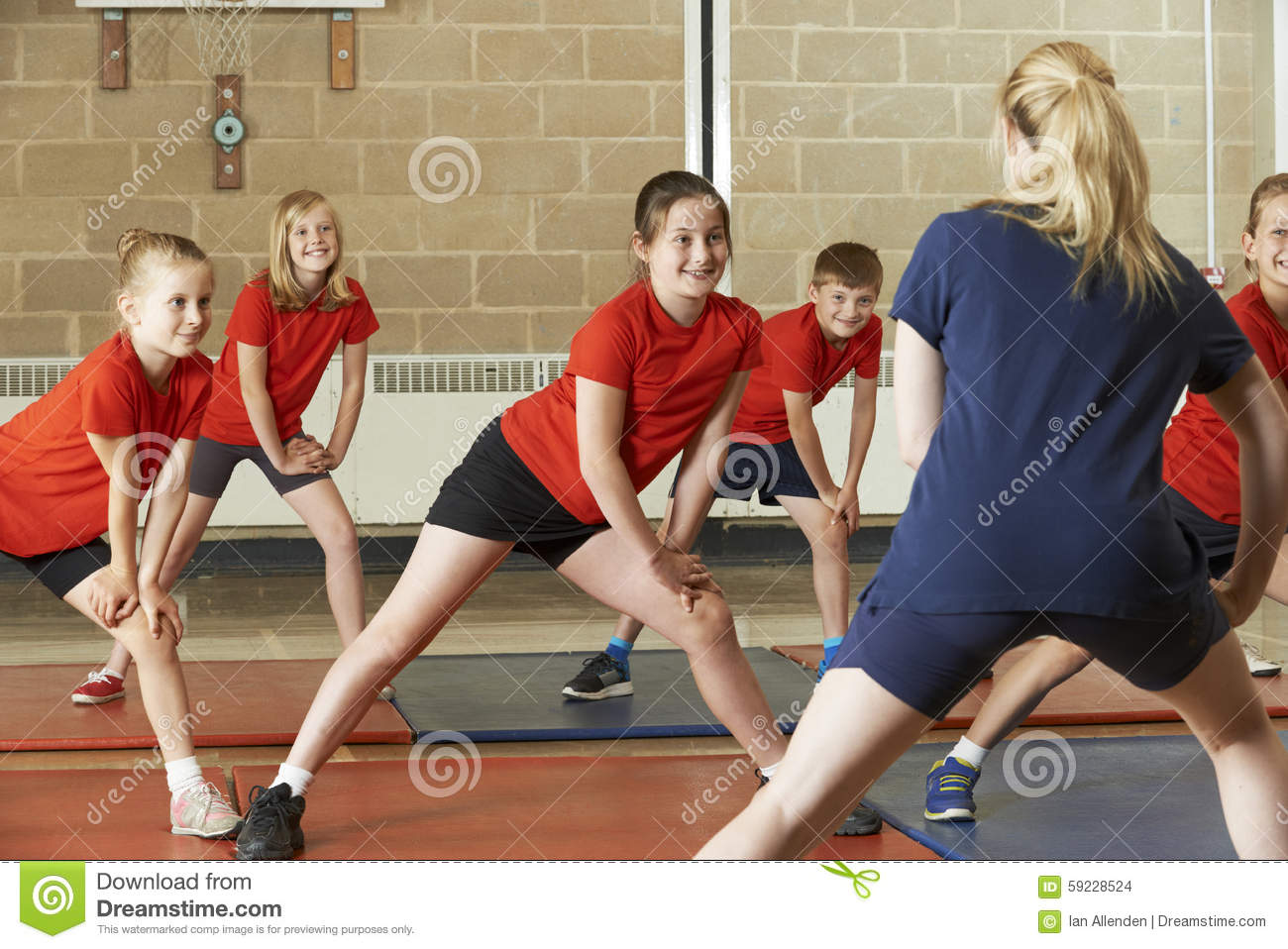Profesor Taking Exercise Class en gimnasio de la escuela