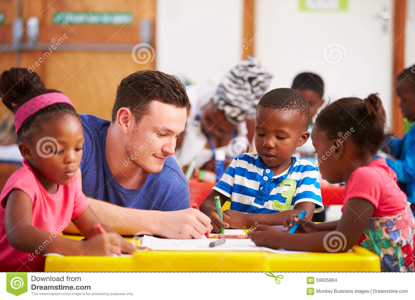 Profesor voluntario que se sienta con los niños preescolares en una sala de clase