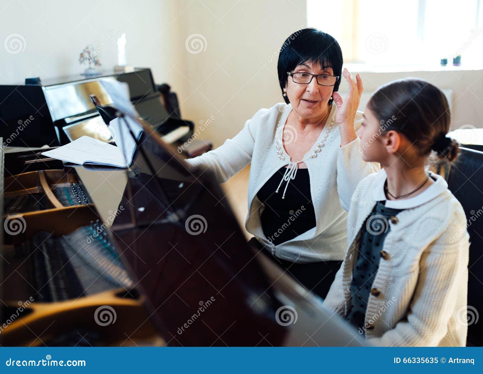 Profesor y alumno en piano de la clase