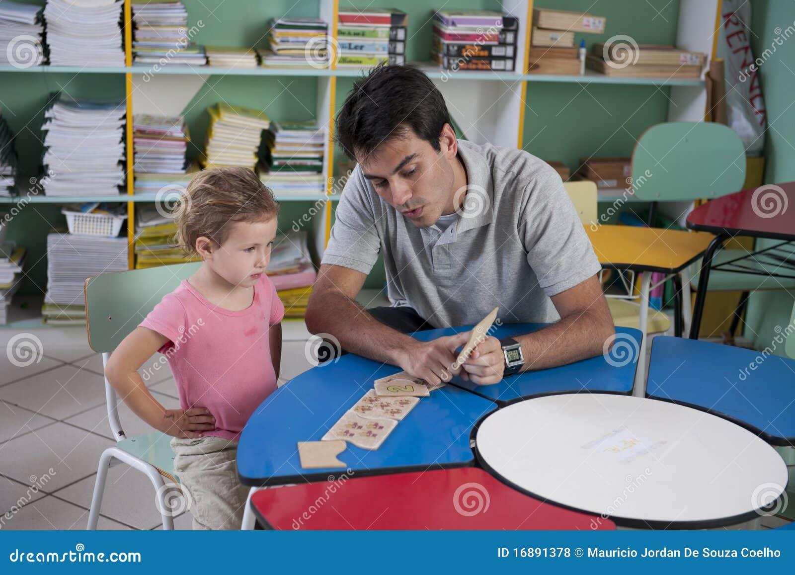 Profesor y niño preescolares en la sala de clase