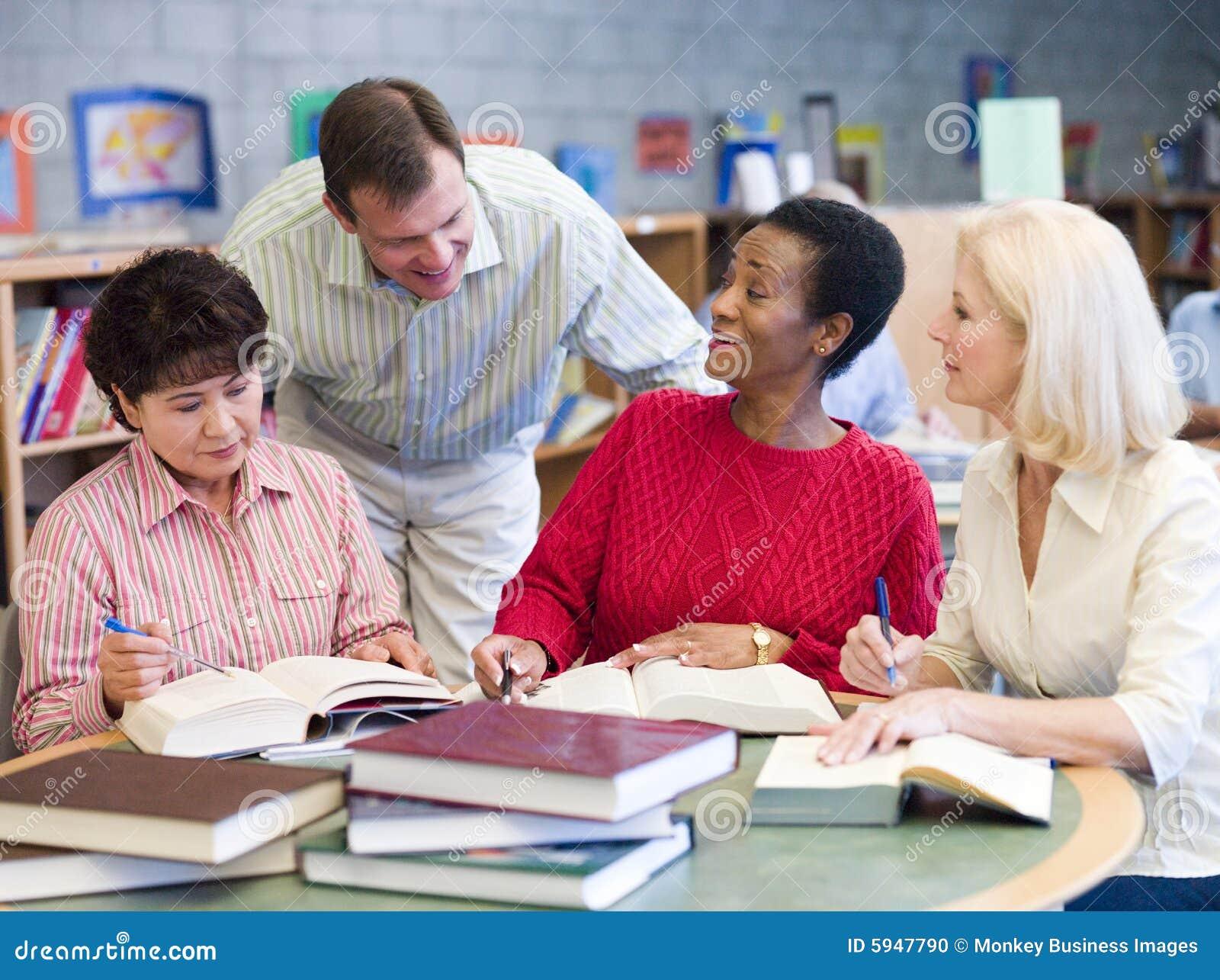 Professeur aidant les étudiants mûrs dans la bibliothèque