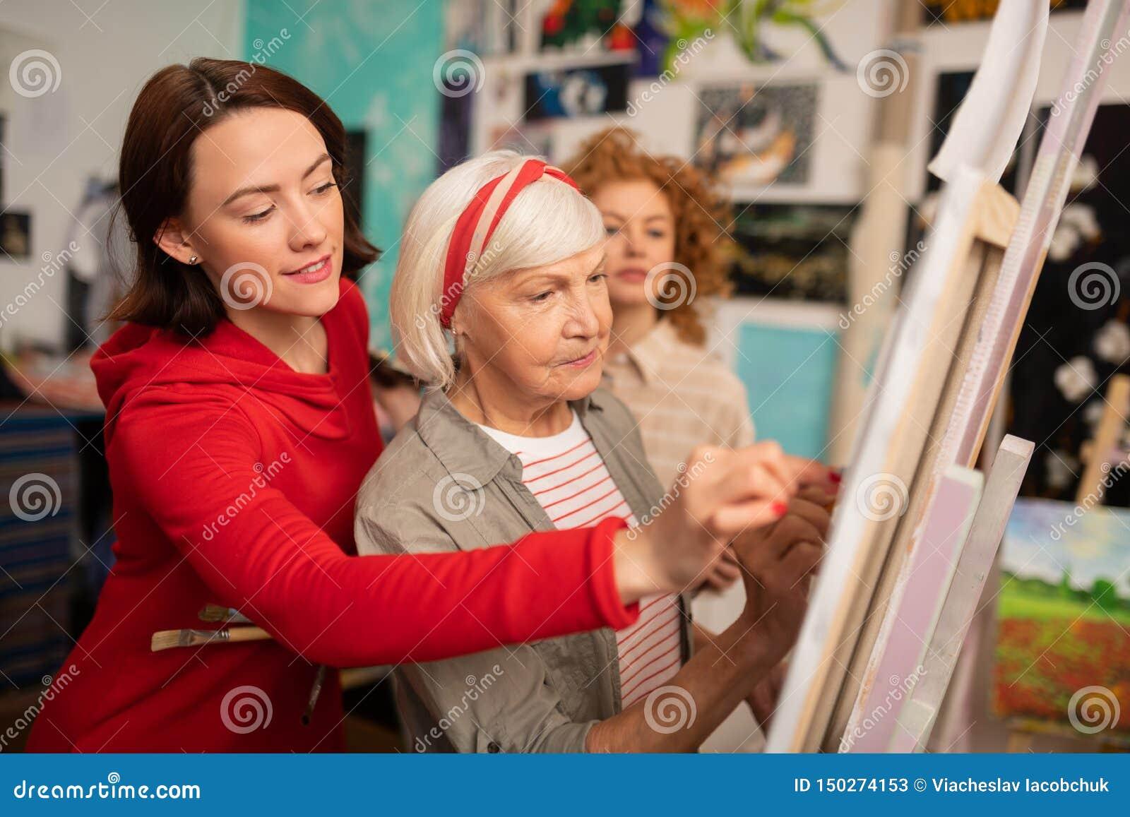 Professeur d art âgé et ses étudiants aidant son dessin sur la toile