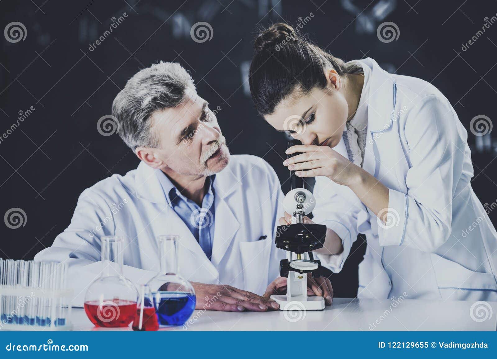 Professeur Explains Student About à l aide du microscope