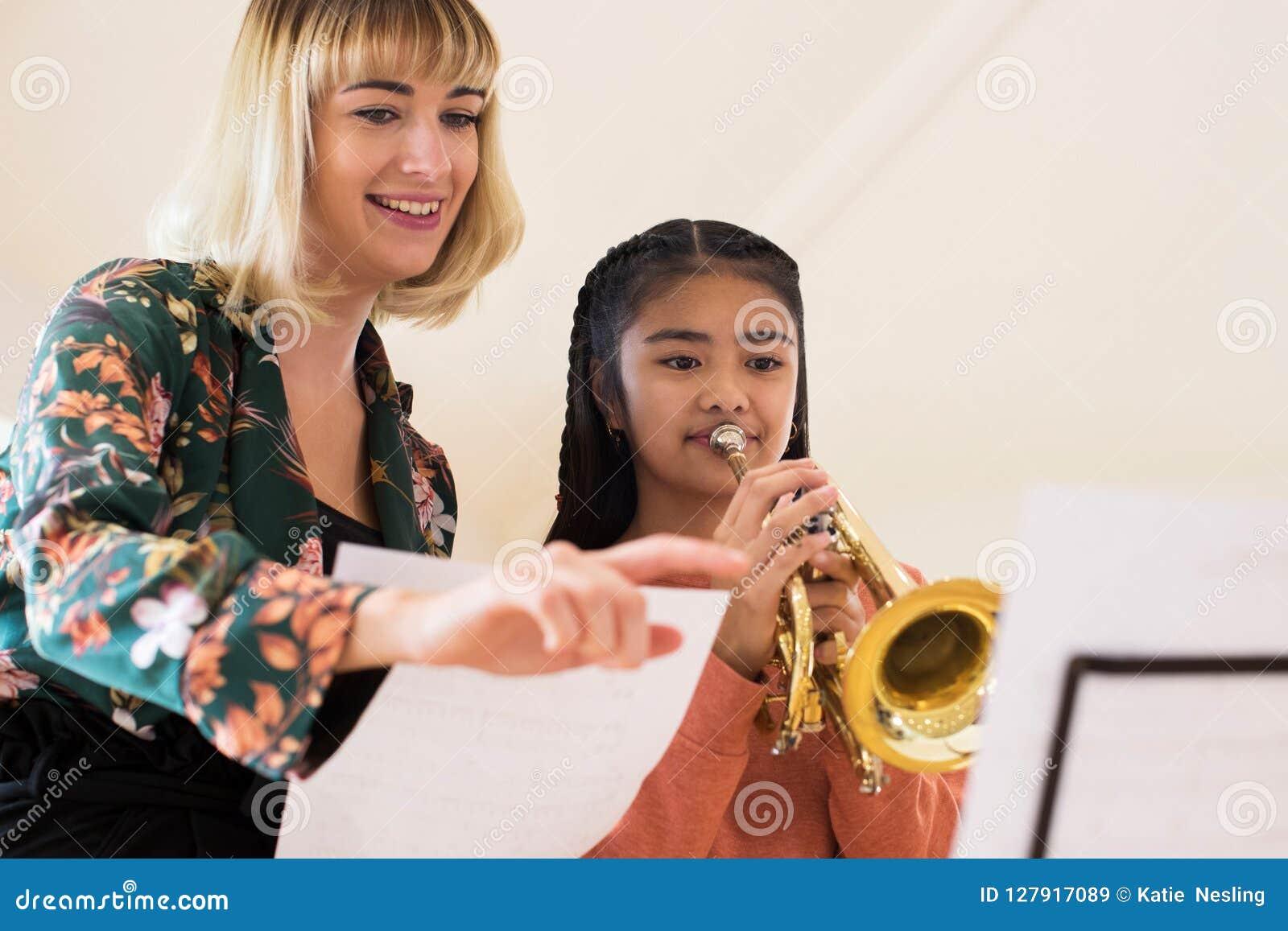 Professeur Helping Female Student pour jouer la trompette dans la leçon de musique