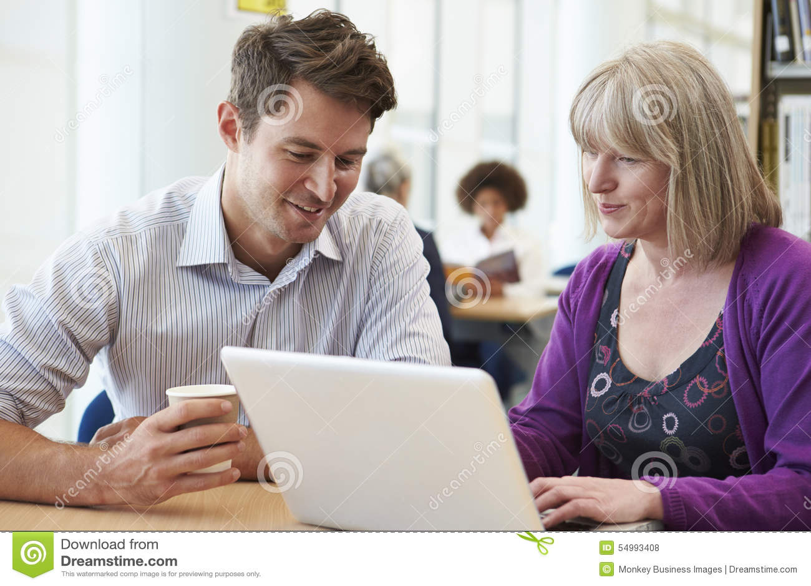 Professeur Helping Mature Student avec des études dans la bibliothèque