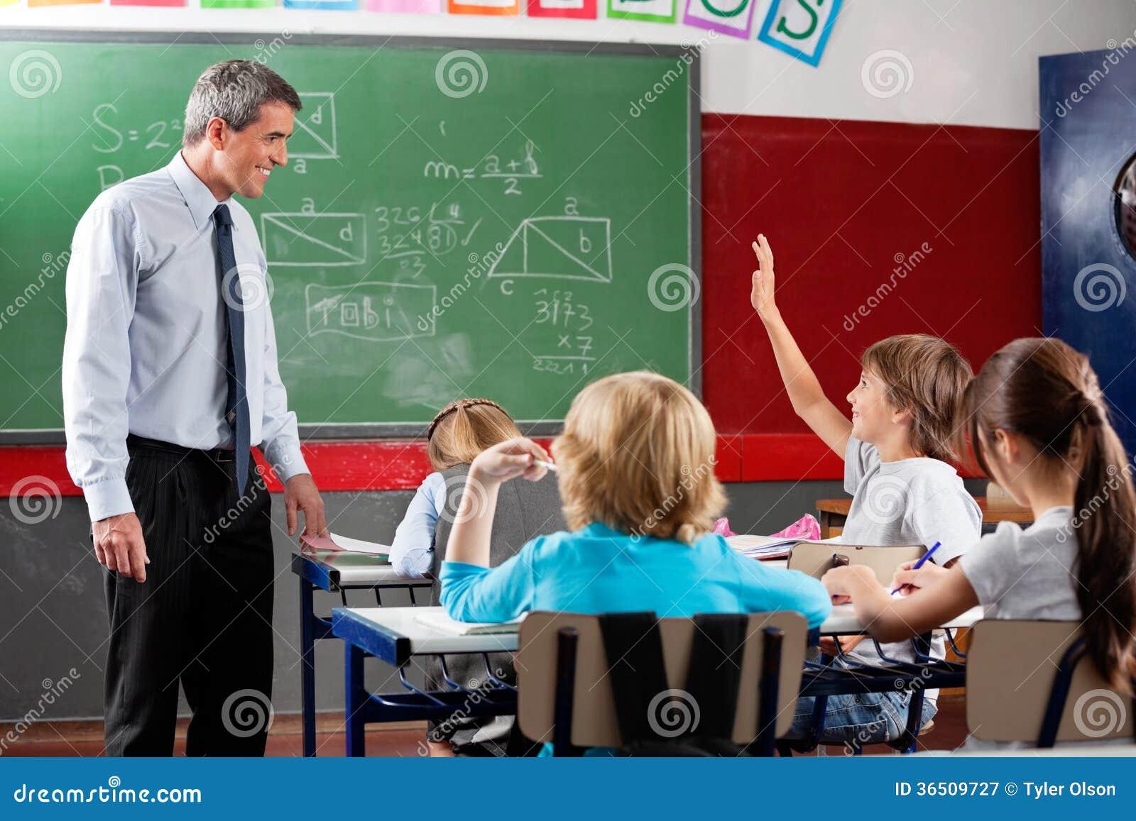 Professeur Looking At Schoolboy soulevant la main