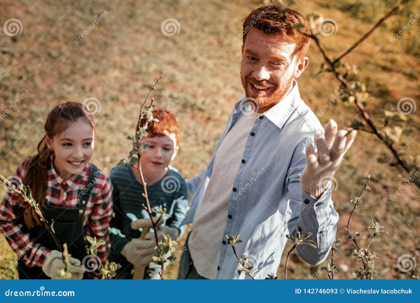 Professeur roux avec la barbe montrant comment élevant des arbres