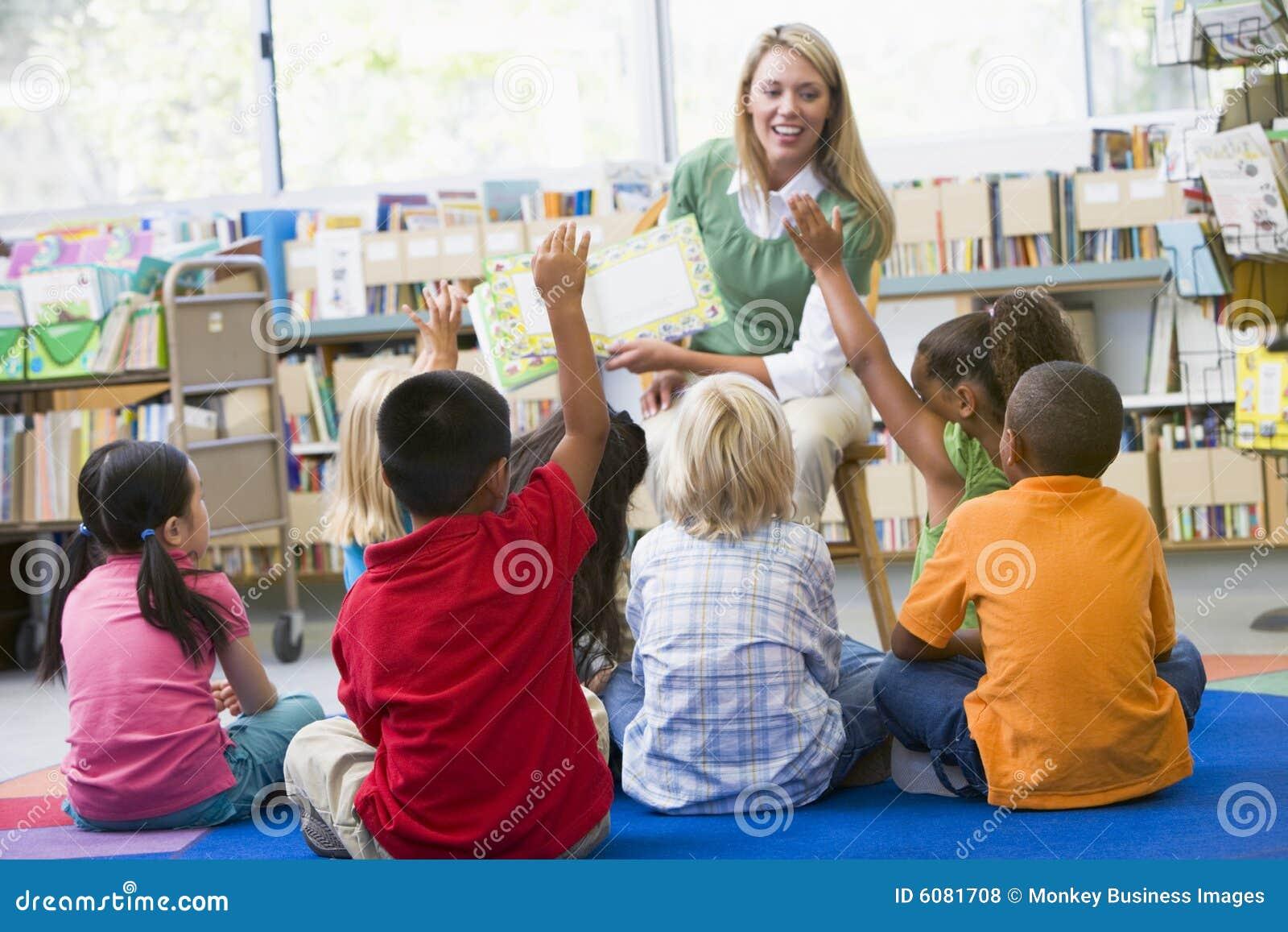 Professeur s affichant aux enfants dans la bibliothèque