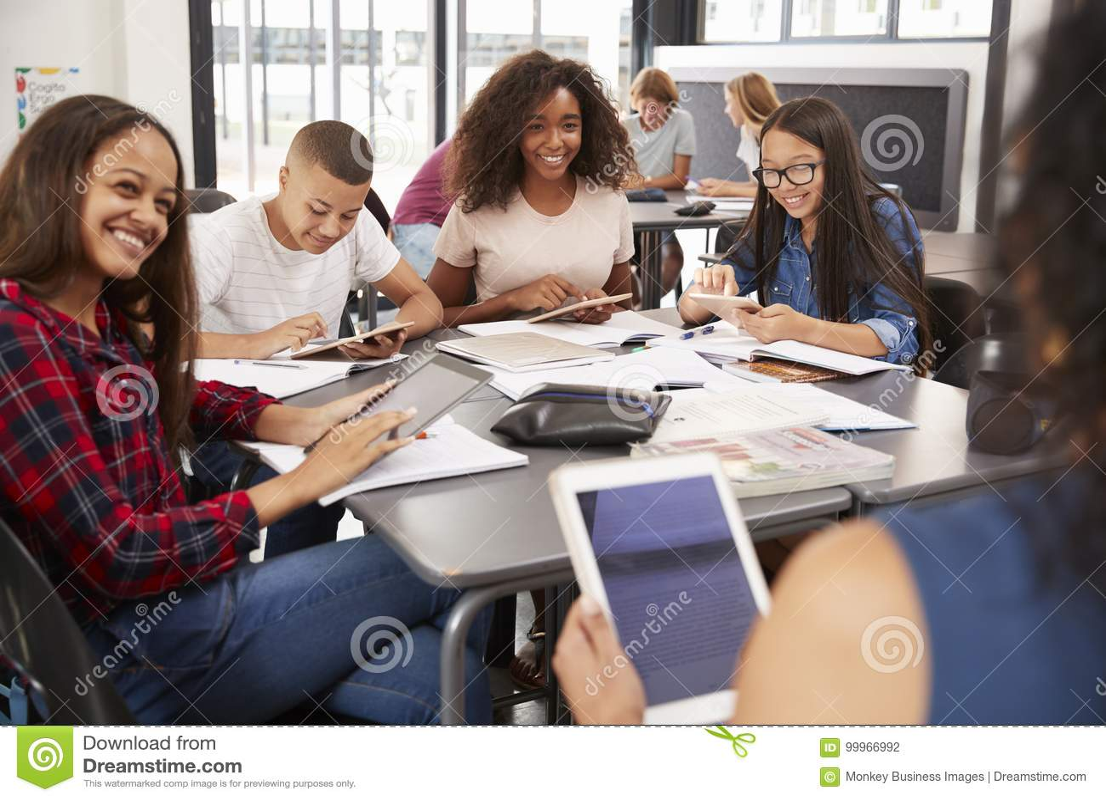 Professeur s asseyant avec des étudiants de lycée à l aide des comprimés