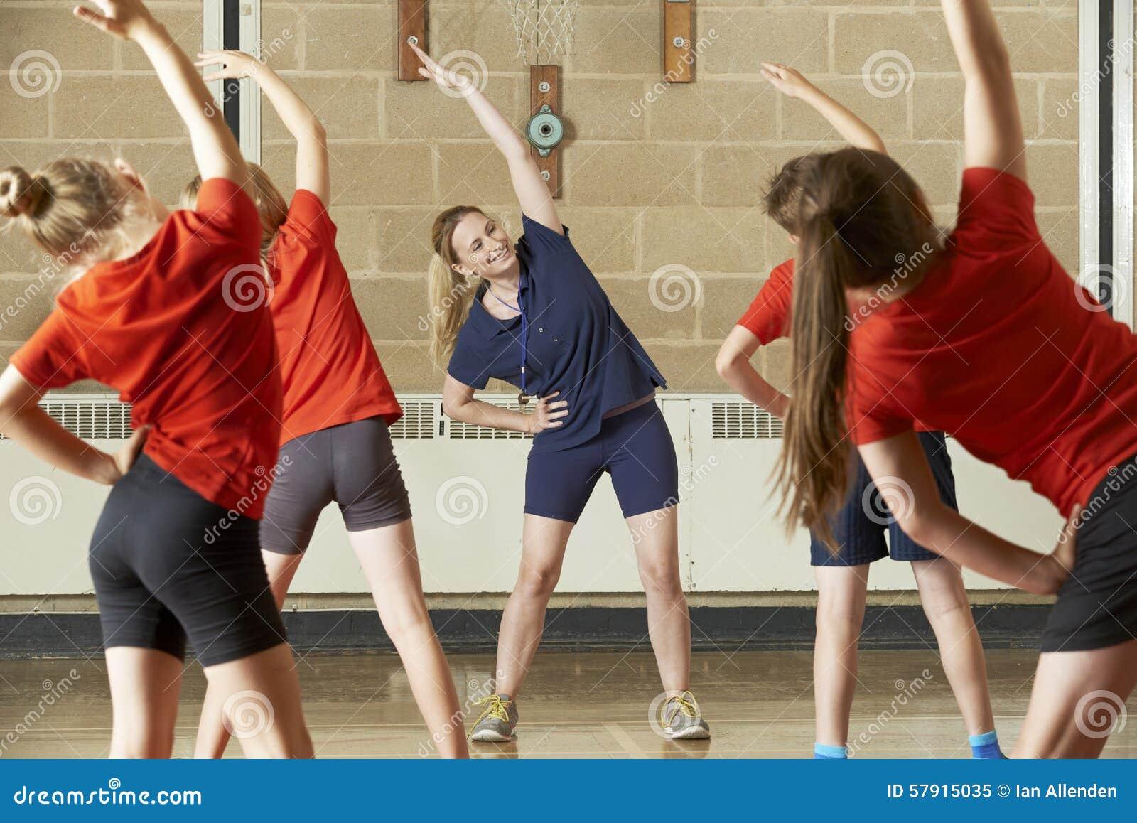 Professeur Taking Exercise Class dans le gymnase d école