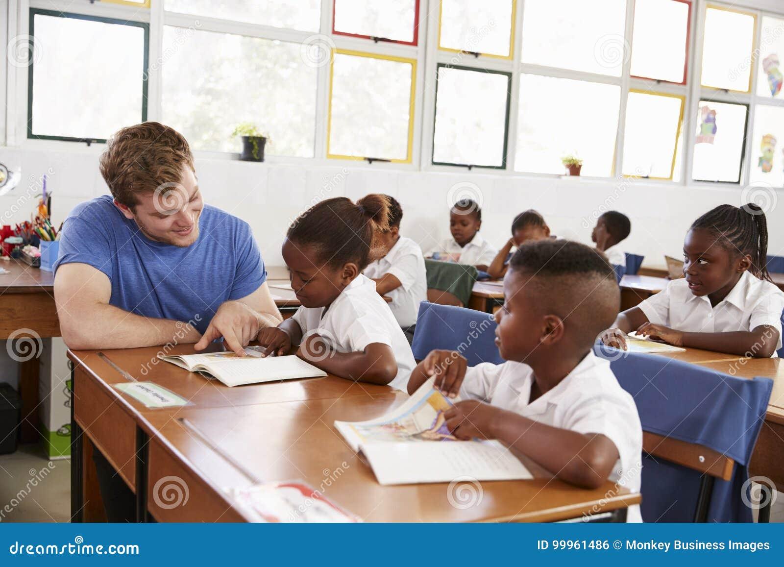 Professeur volontaire aidant la jeune fille à son bureau dans la classe