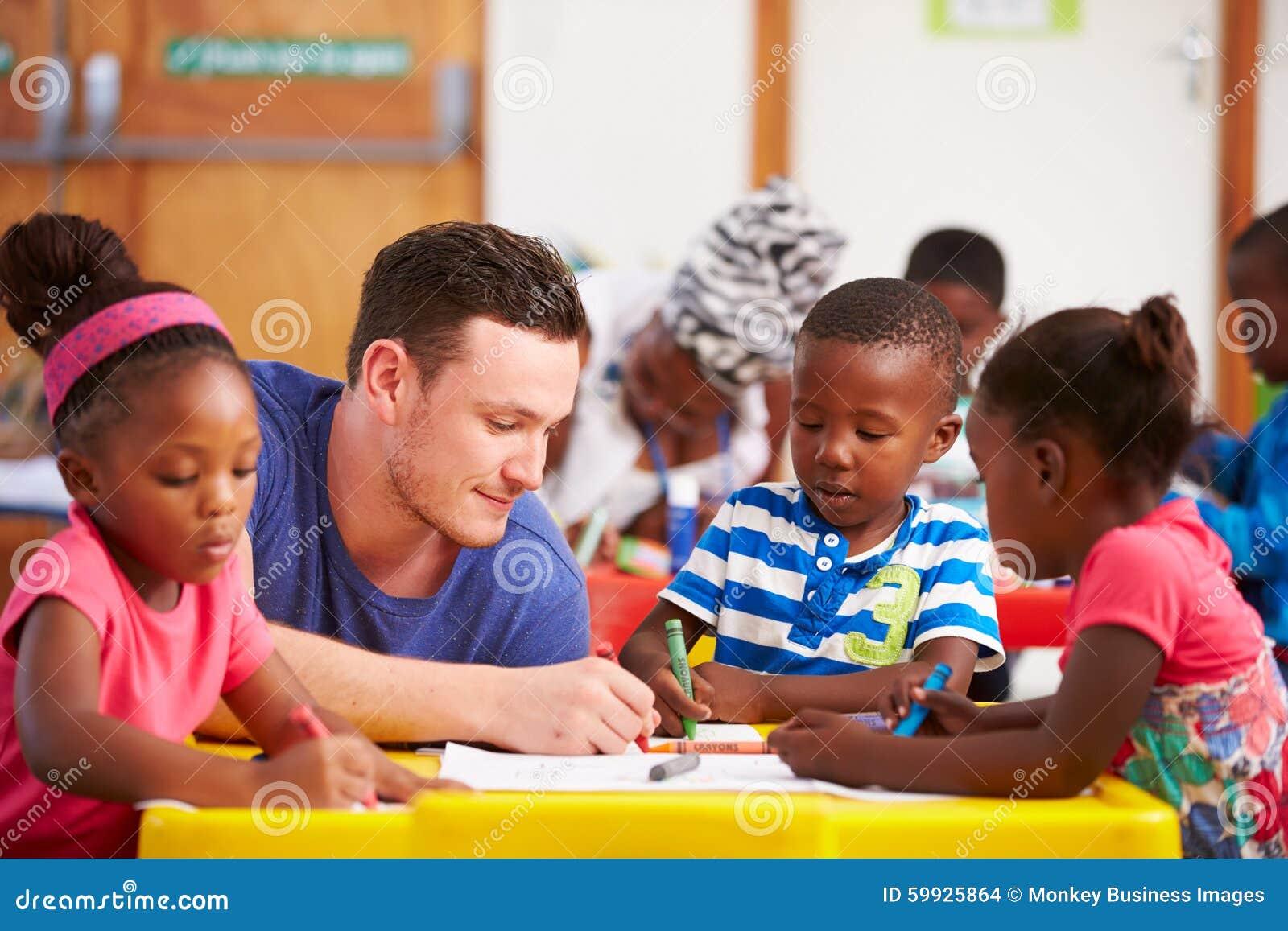 Professeur volontaire s asseyant avec les enfants préscolaires dans une salle de classe