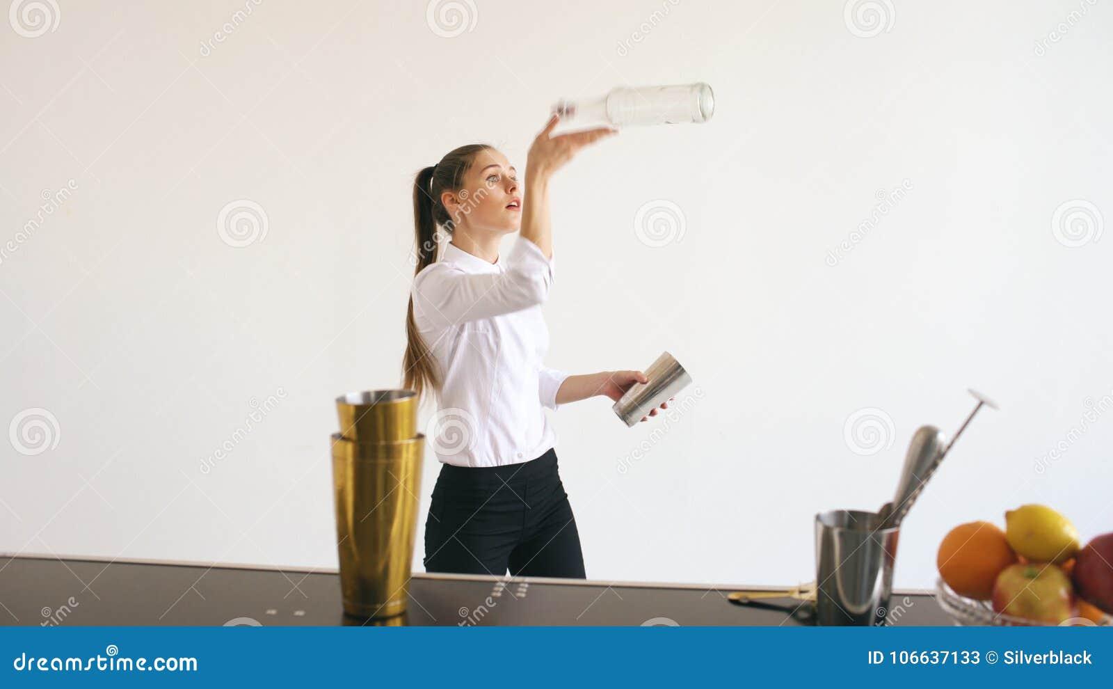 Professinal侍酒者女孩玩杂耍的瓶和震动鸡尾酒在白色背景的流动酒吧桌上