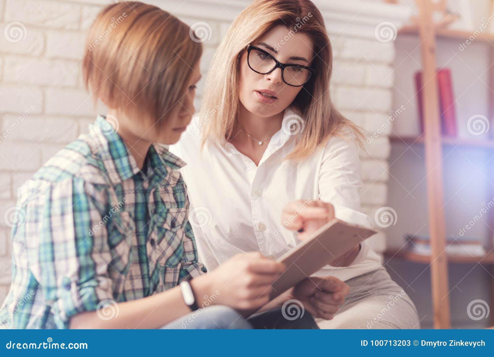 Professioanl kvinnlig psykologgivign ett prov till en skolpojke