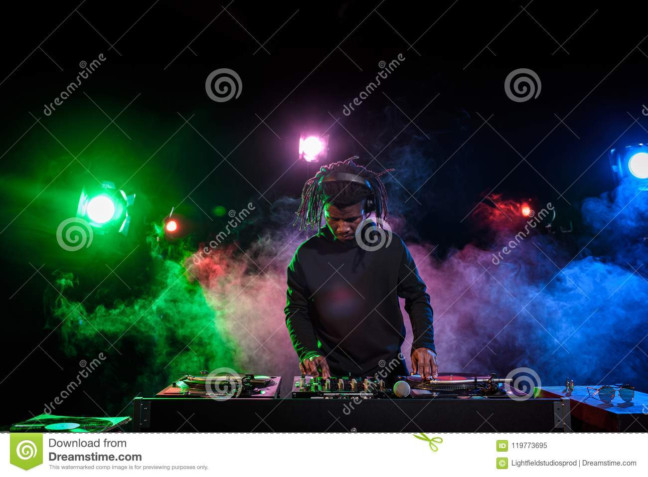 professional african american club DJ in headphones with sound mixer