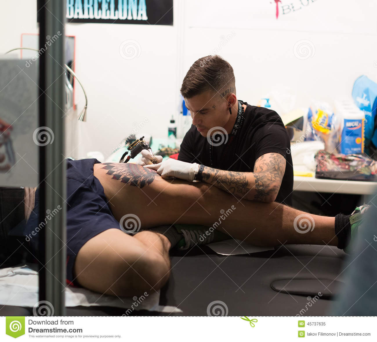 Professional artist doing colorful tattoo on male client s leg
