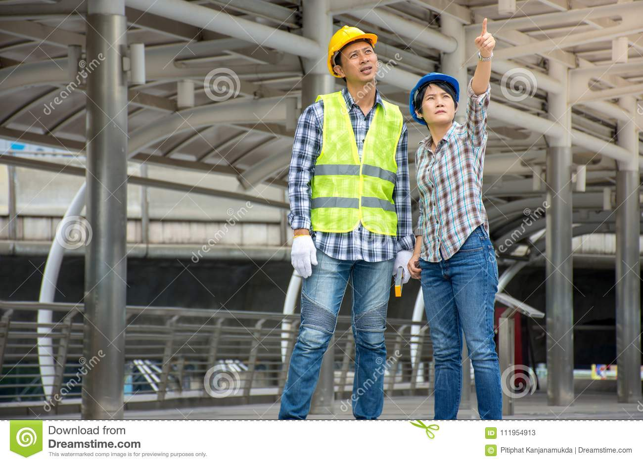 Professional Asian engineering team wearing safety helmet talking about construction project and pointing finger up at