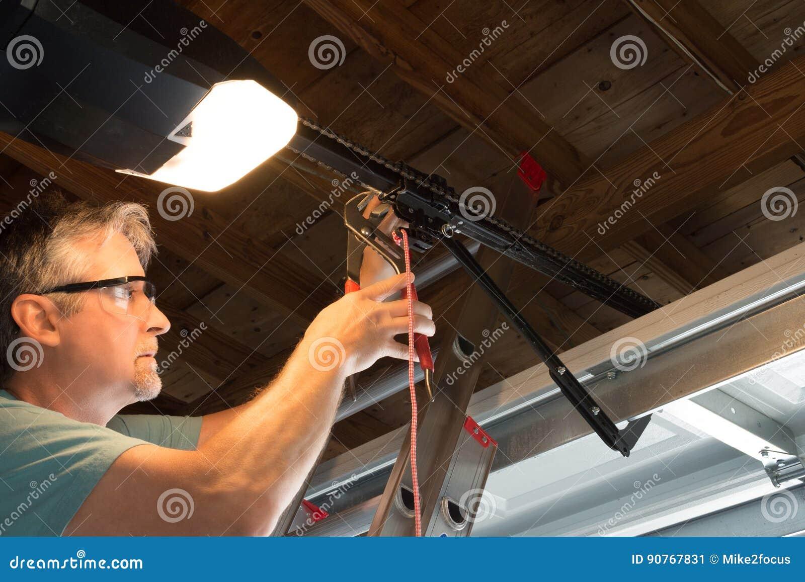 Professional automatic garage door opener repair service technician working closeup