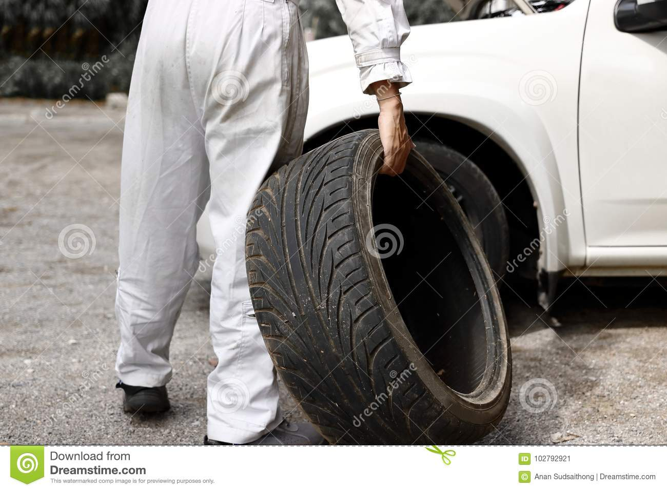 Professional Automotive Mechanic In Uniform Holding Tire For Fixing