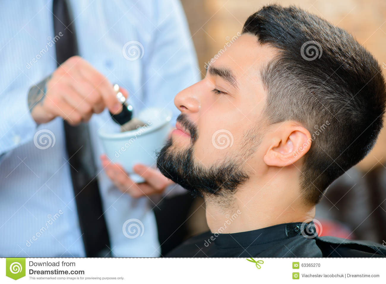 professional barber shaving the beard of his stock photo image 63365270. Black Bedroom Furniture Sets. Home Design Ideas