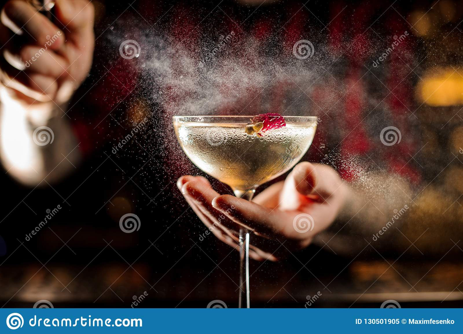Professional bartender spraying on a Twinkle cocktail in the bar