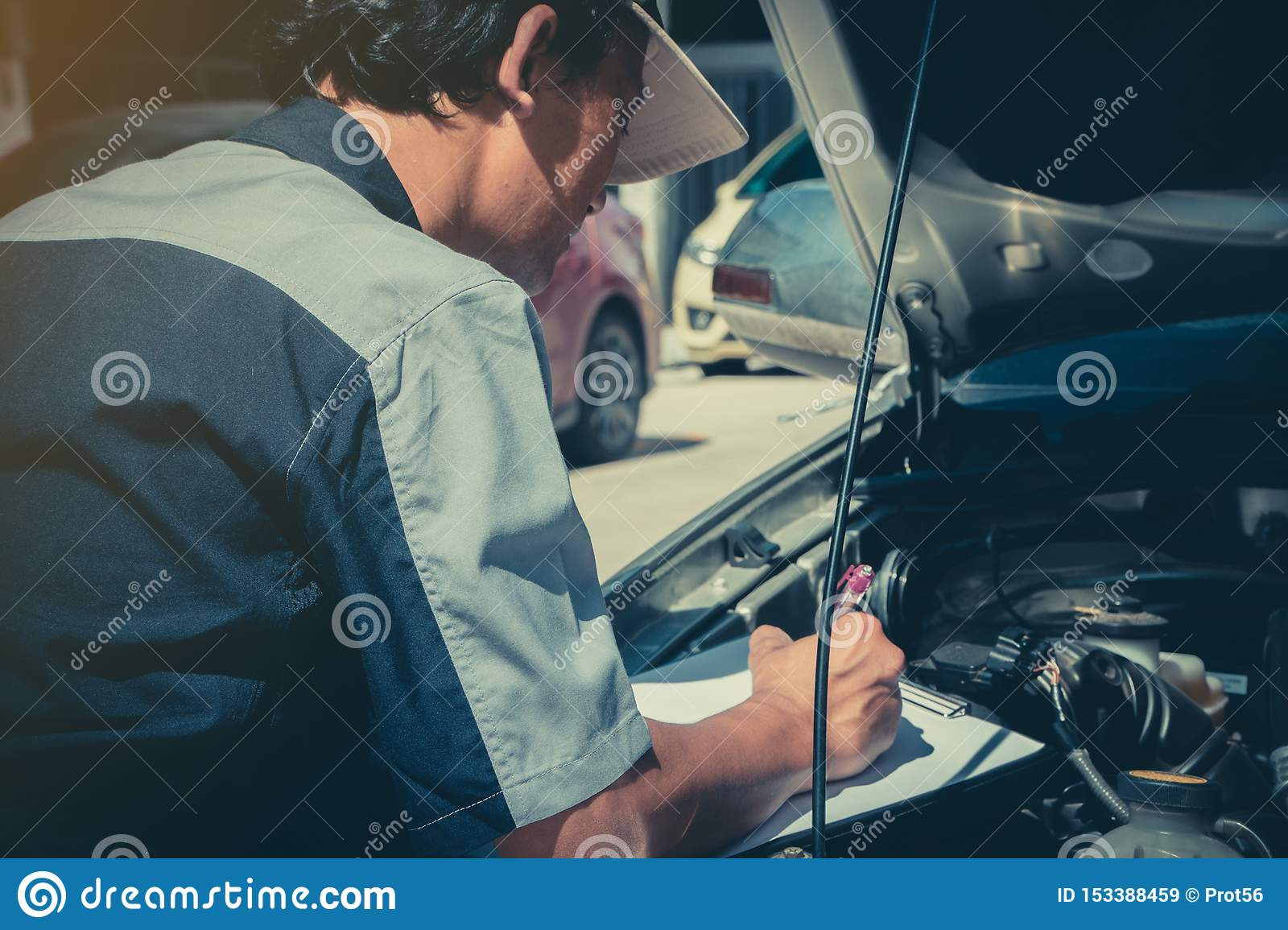Professional car repair technicians inspect the engine according to the checklist documents to ensure that they are inspected acco