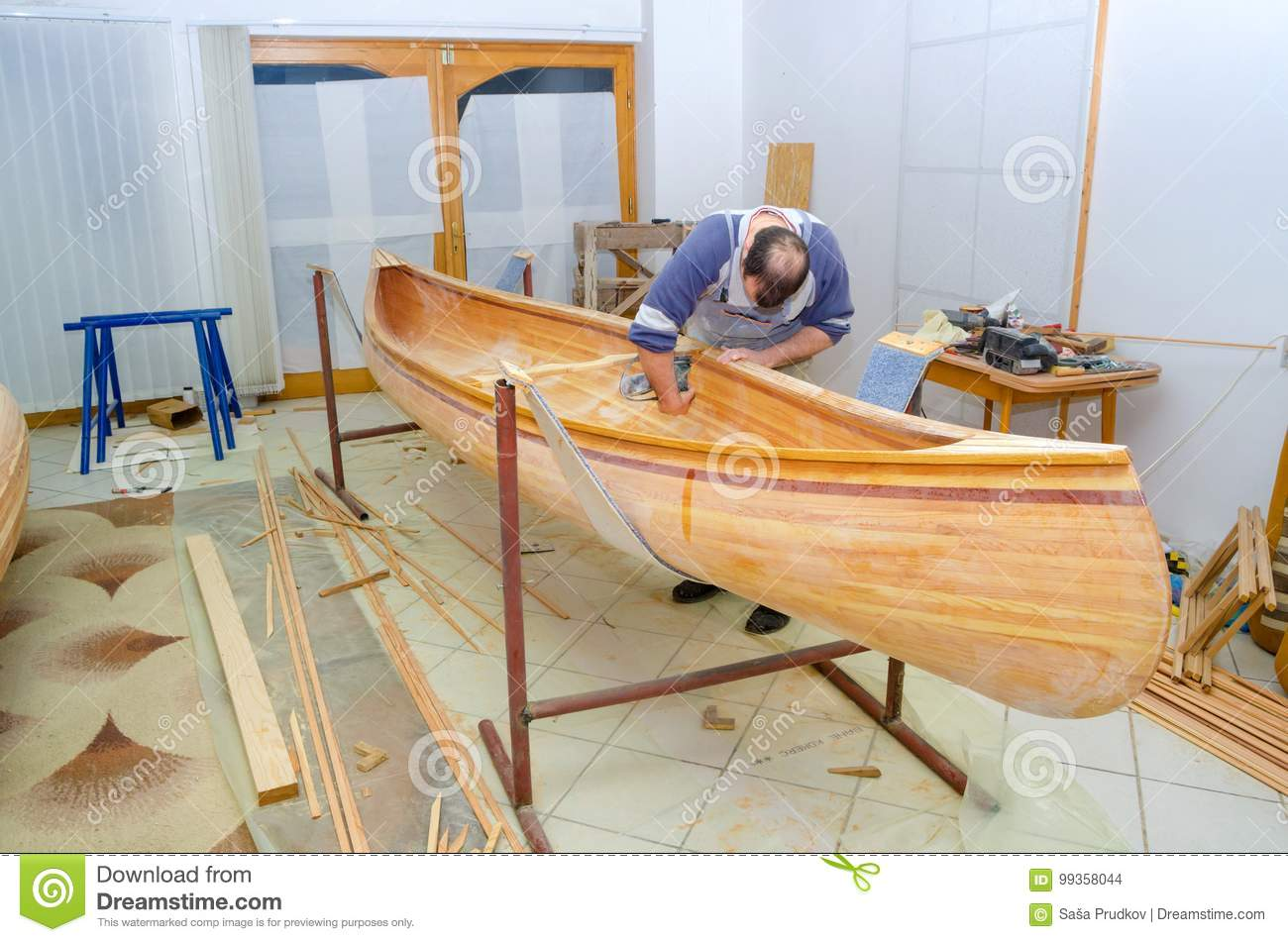 Professional Carpenter Making Wooden Canoe In His Workshop Stock