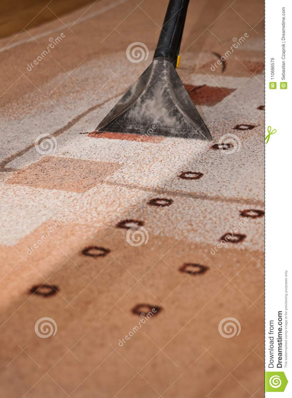 Closeup of a professional carpet cleaning machine, working end tool, lighter stripe of cleaner carpet abstract.