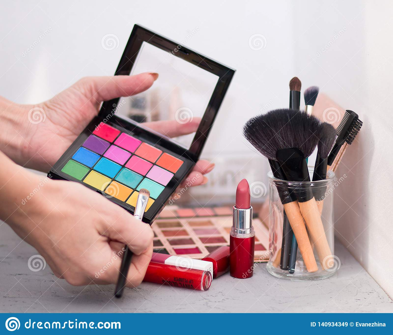 Professional cosmetic brushes, shadows, lipsticks and sponges on a gray table