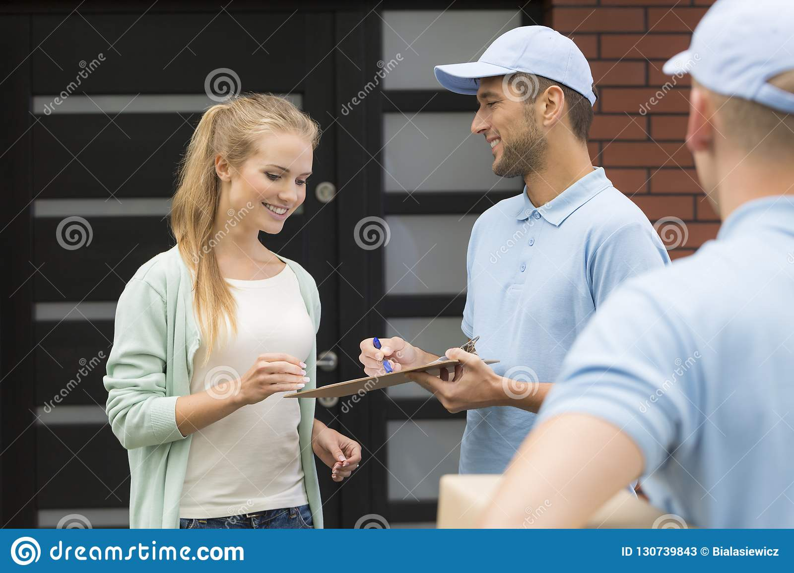 Professional couriers delivering package to smiling woman