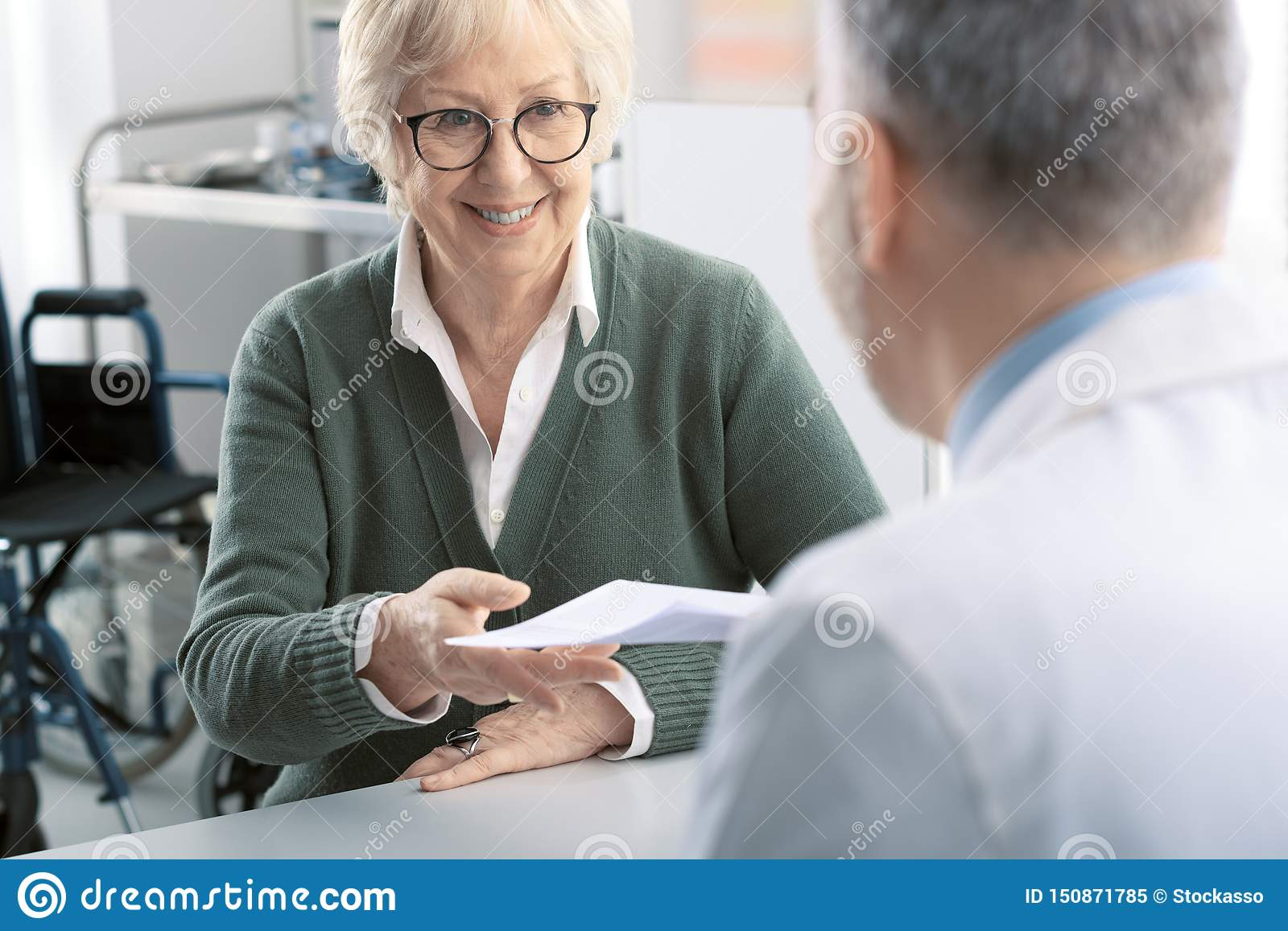 Professional doctor giving a prescription to a senior patient