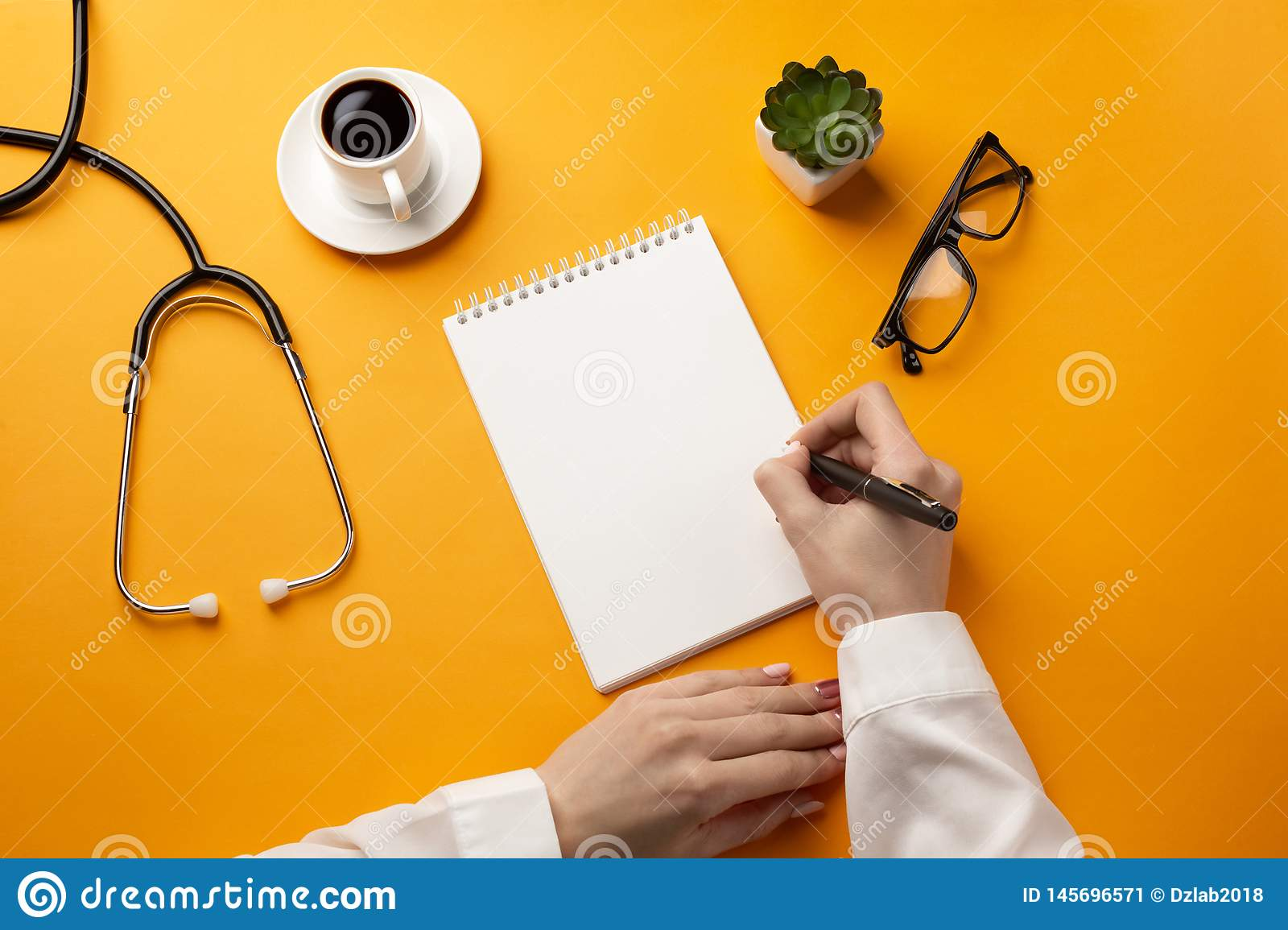 Professional doctor writing medical records in a notebook with stethoscope, coffee cup and glasses