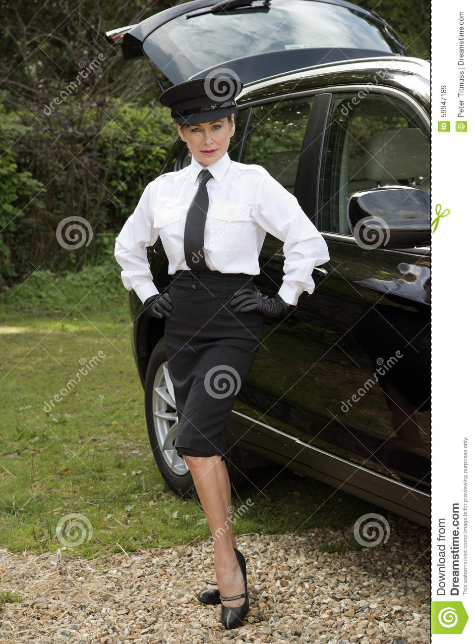 professional driver standing with hands on hips by her car. Black Bedroom Furniture Sets. Home Design Ideas