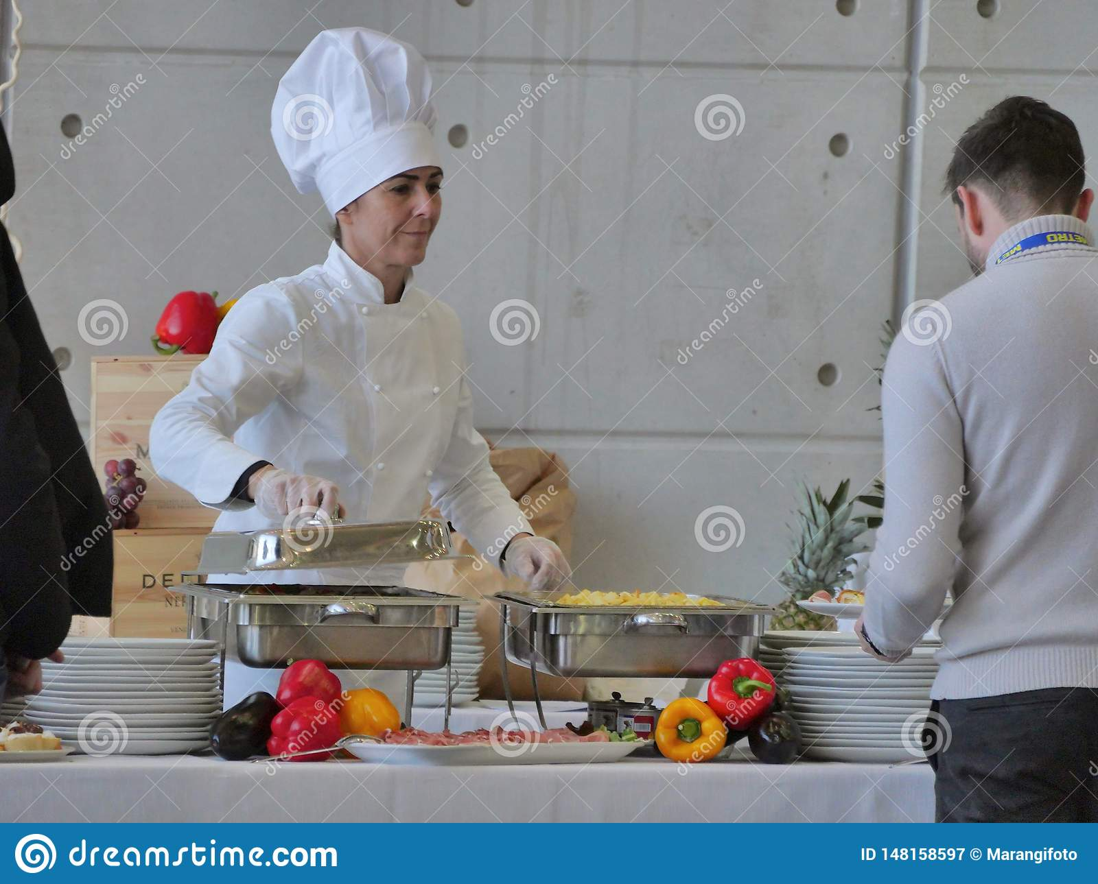 Professional female chef prepares buffet food for customers