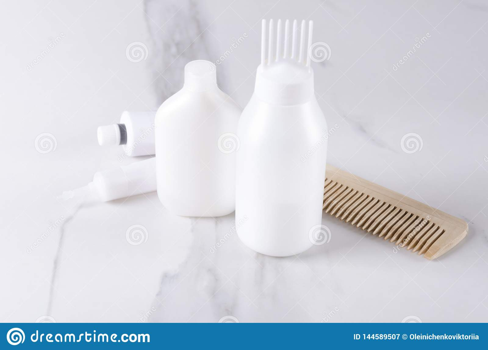 Professional hair care products,tubes for dye hair,wooden comb on white marble table.Concept of dye hair