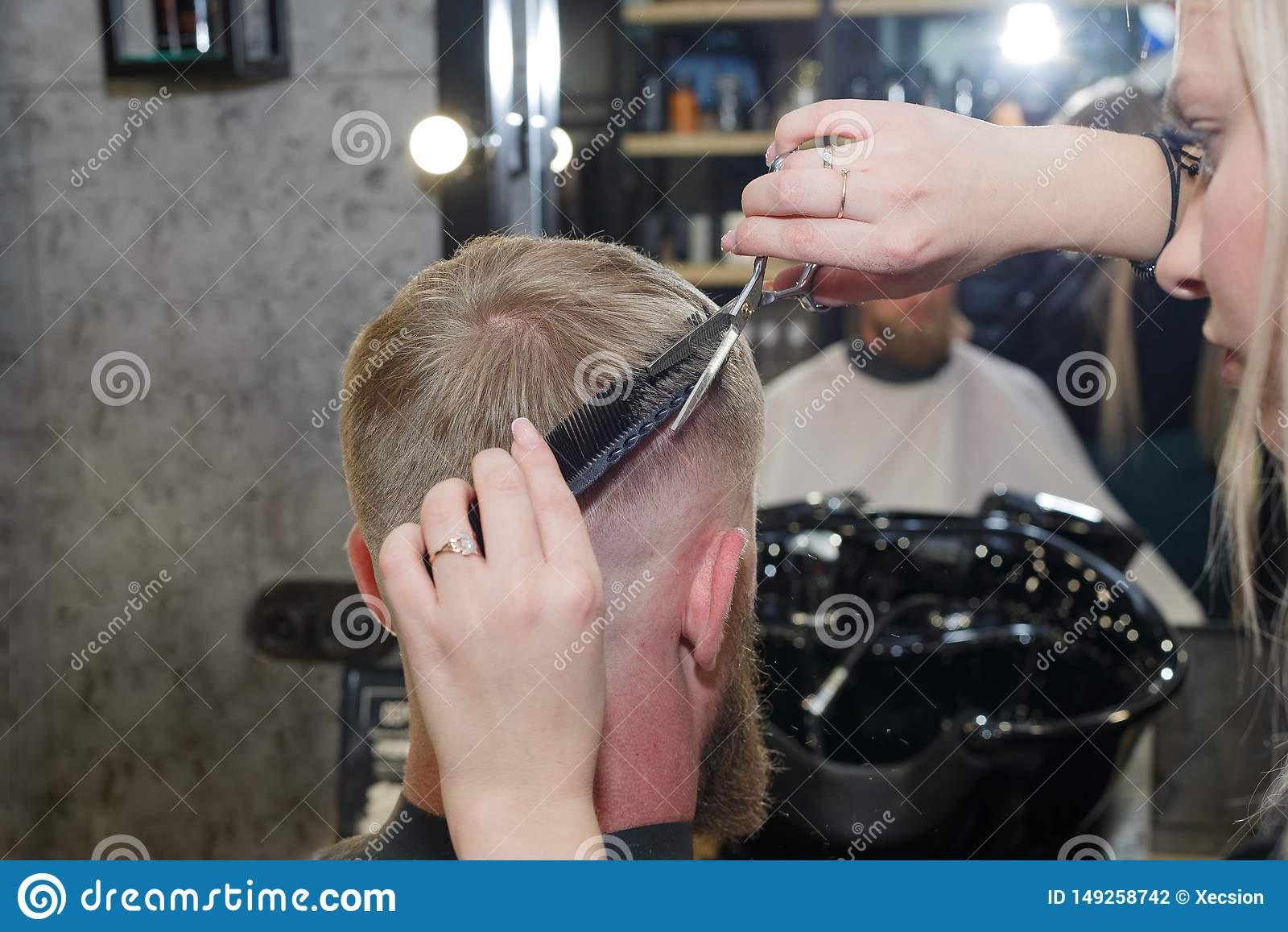 Professional hairdresser hair styling of their client. The master provides a haircut.