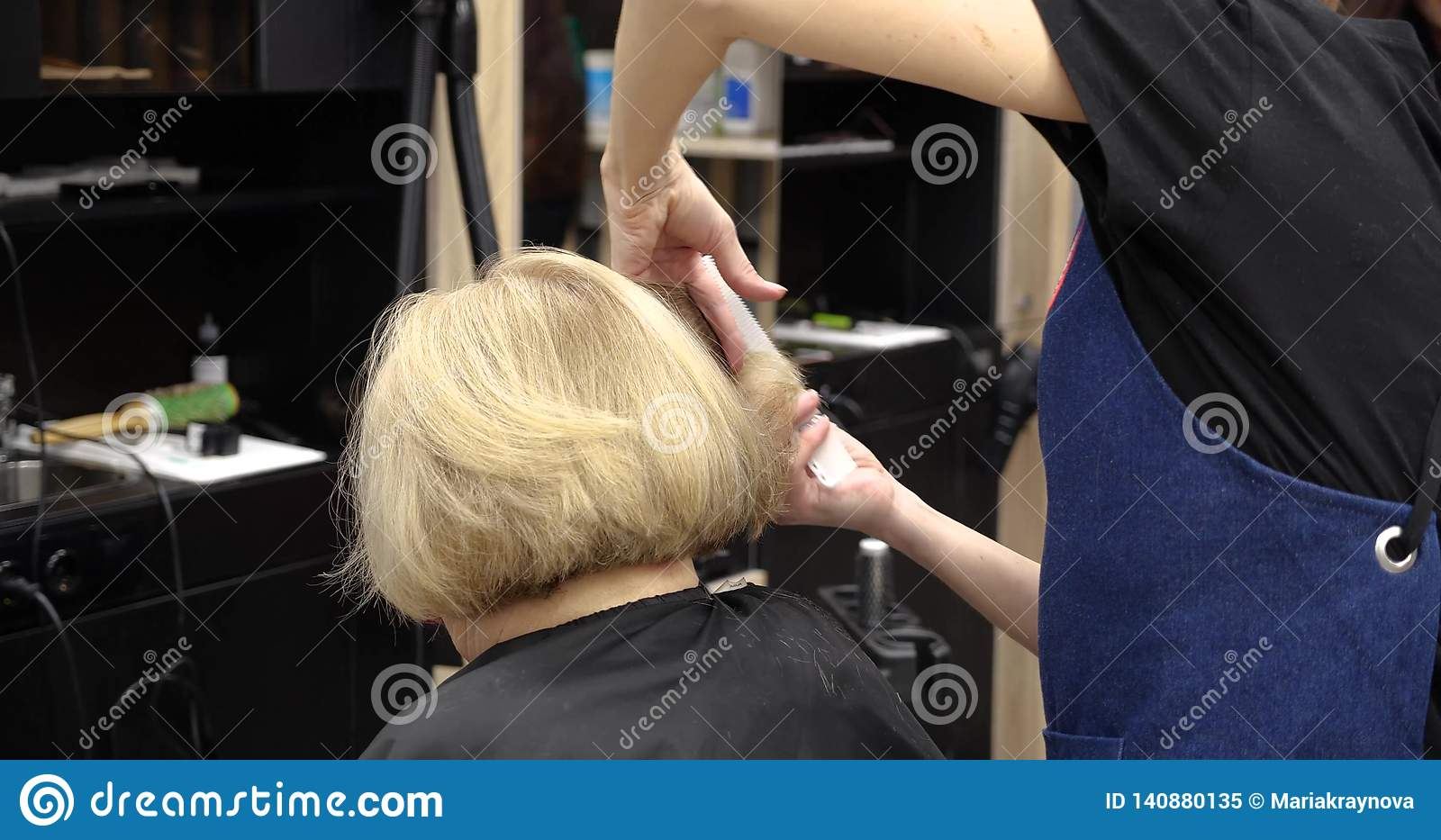 Professional hairdresser, stylist combing hair of female client and cutting hair in professional hair salon