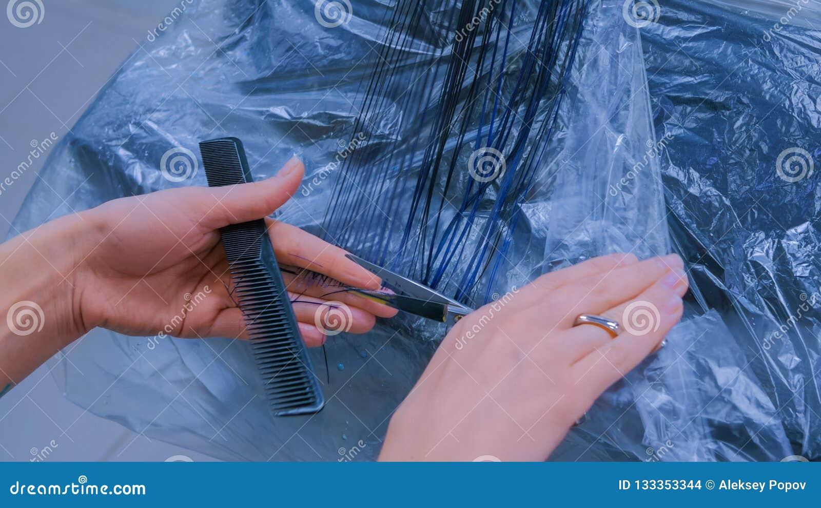 Hairdresser cutting hair of woman client