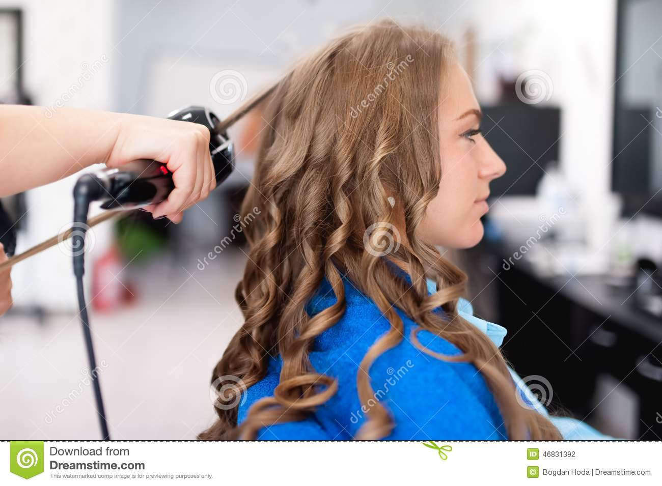 Professional Hairdresser Using Curling Iron For Hair Curls