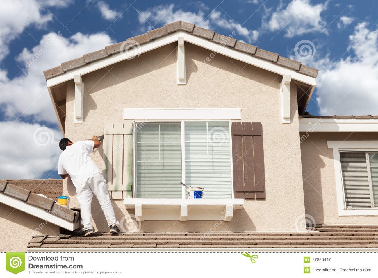 Professional House Painter Painting the Trim And Shutters of A H