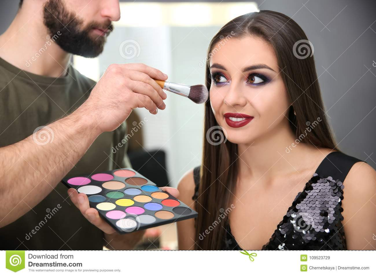 Professional Makeup Artist Working With Attractive Woman Indoors