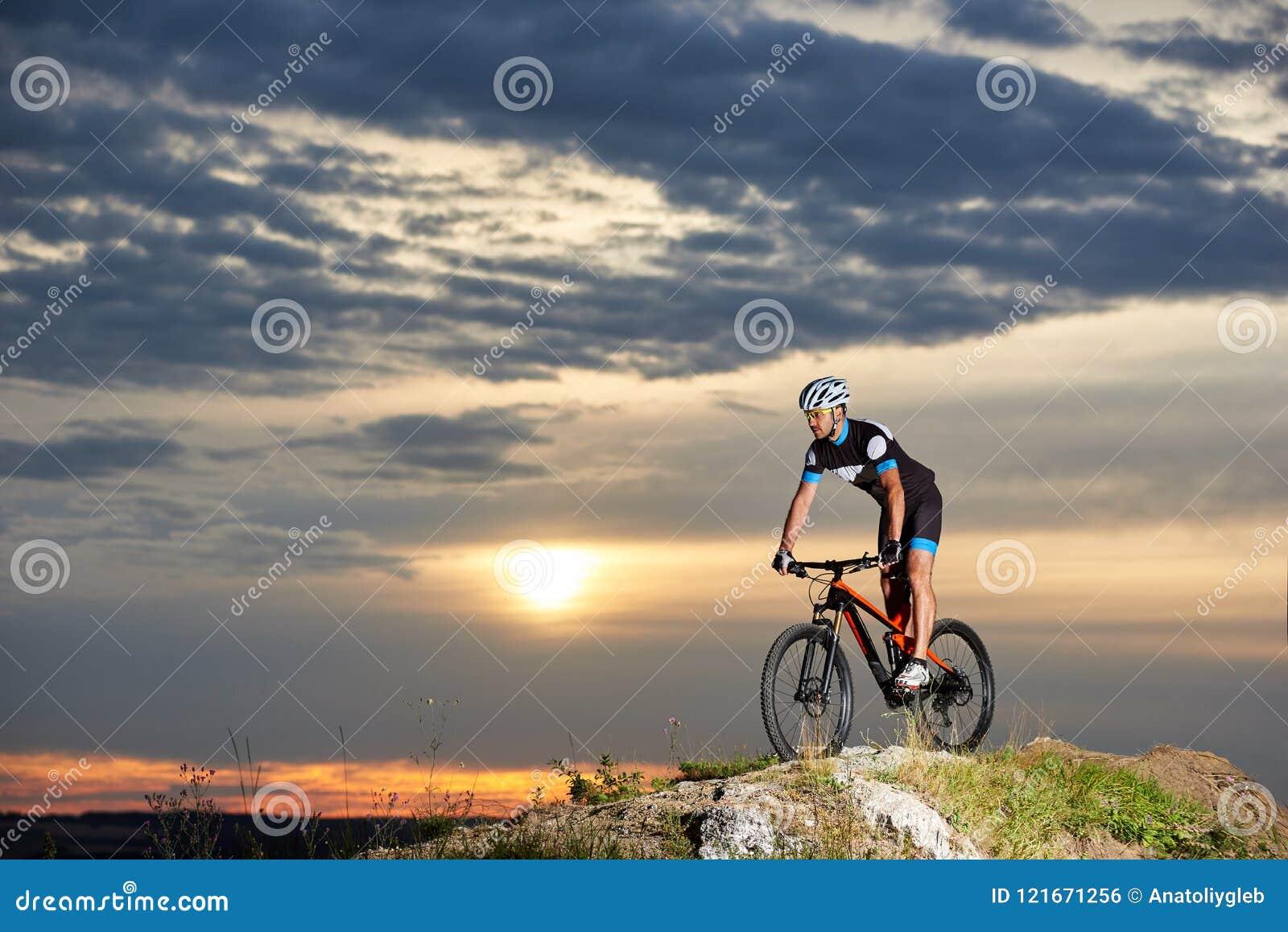 Energetic man in sportswear cycling on rock hill.
