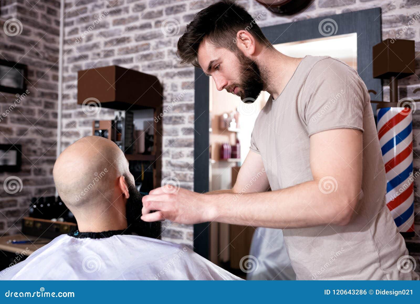 Professional Master hairdresser cuts client beard