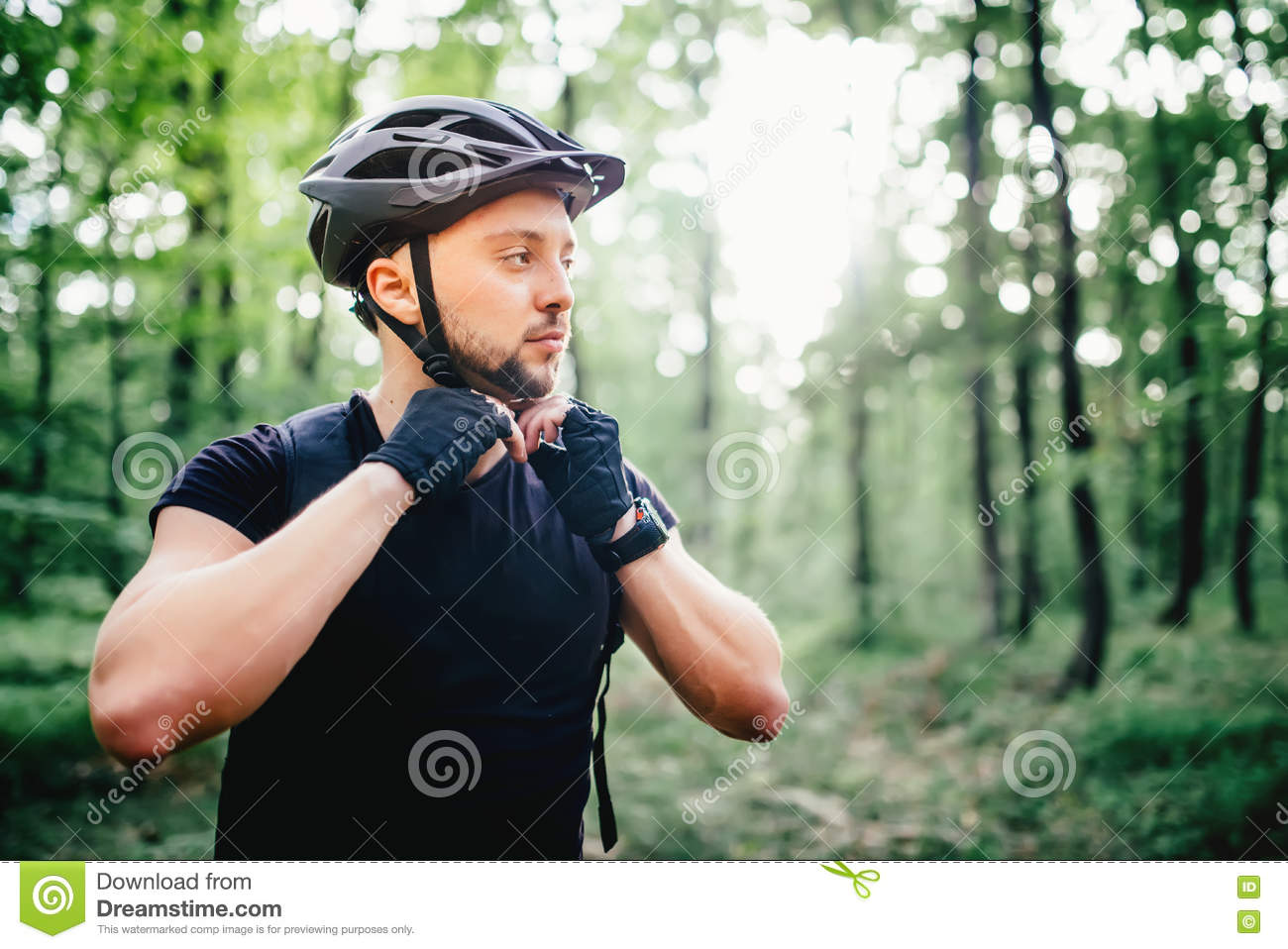 Professional mountain bike rider, cyclist preparing protection helmet during workout