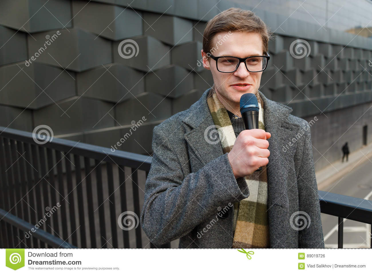 Professional news reporter in eyeglasses with microphone is broadcasting on the street. Fashion or business news