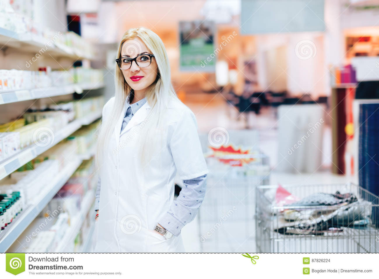 Professional pharmacist standing in pharmacy drugstore and smiling. Details of pharmaceutical industry