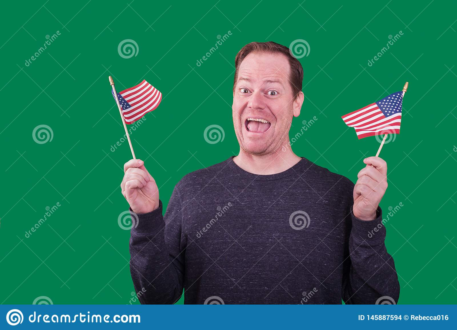 Patriotic man waving two American flags excited happy facial expression on green screen background