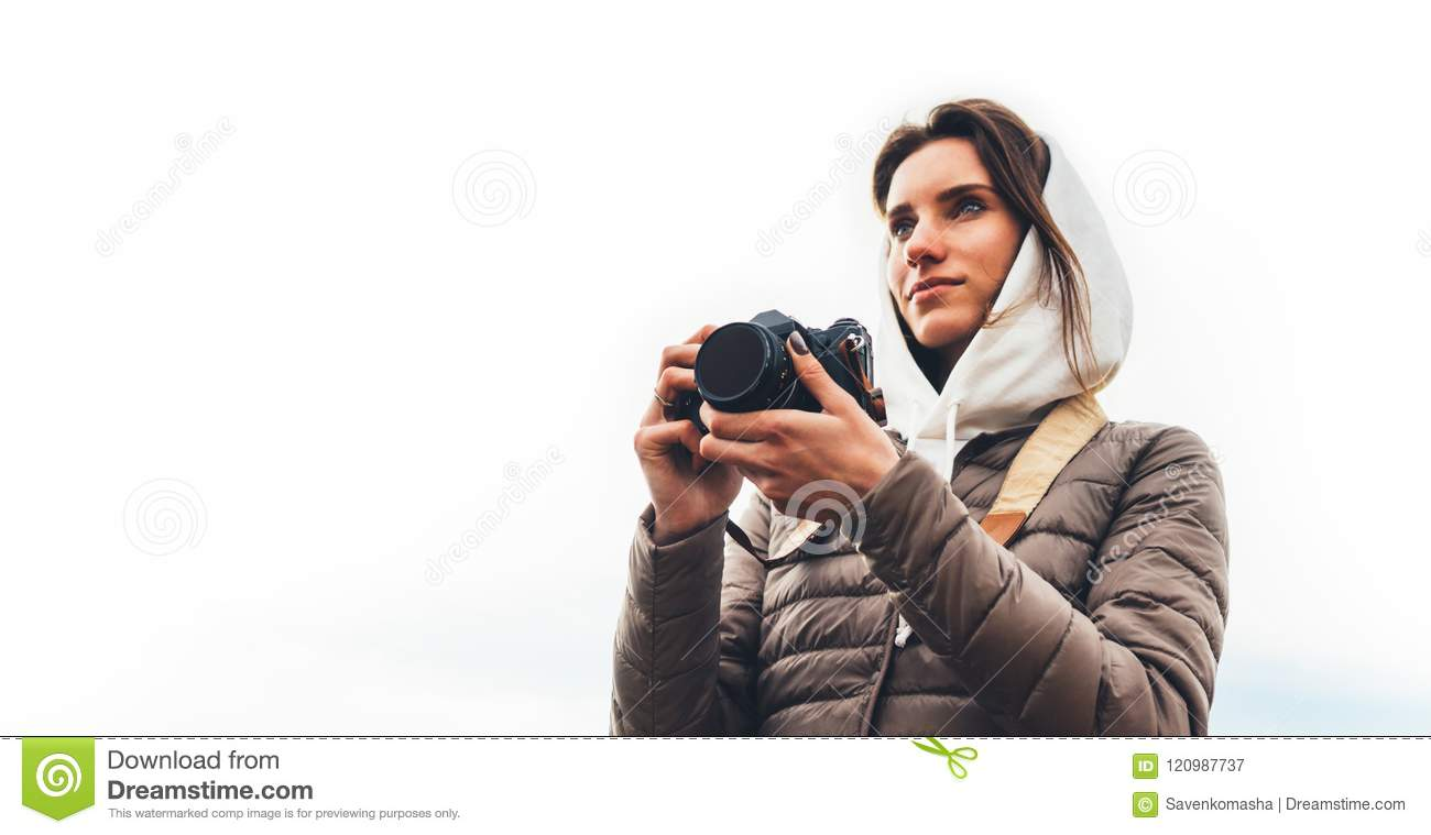 Professional photographer tourist traveler standing on on a white background holding in hands digital photo camera, hiker view fro