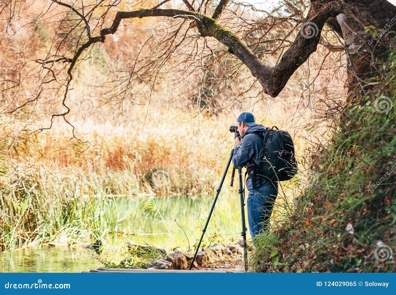 Professional photographer using a tripod takes a shot of the autumn lakes in Plitvice Lakes National Park, Croatia.