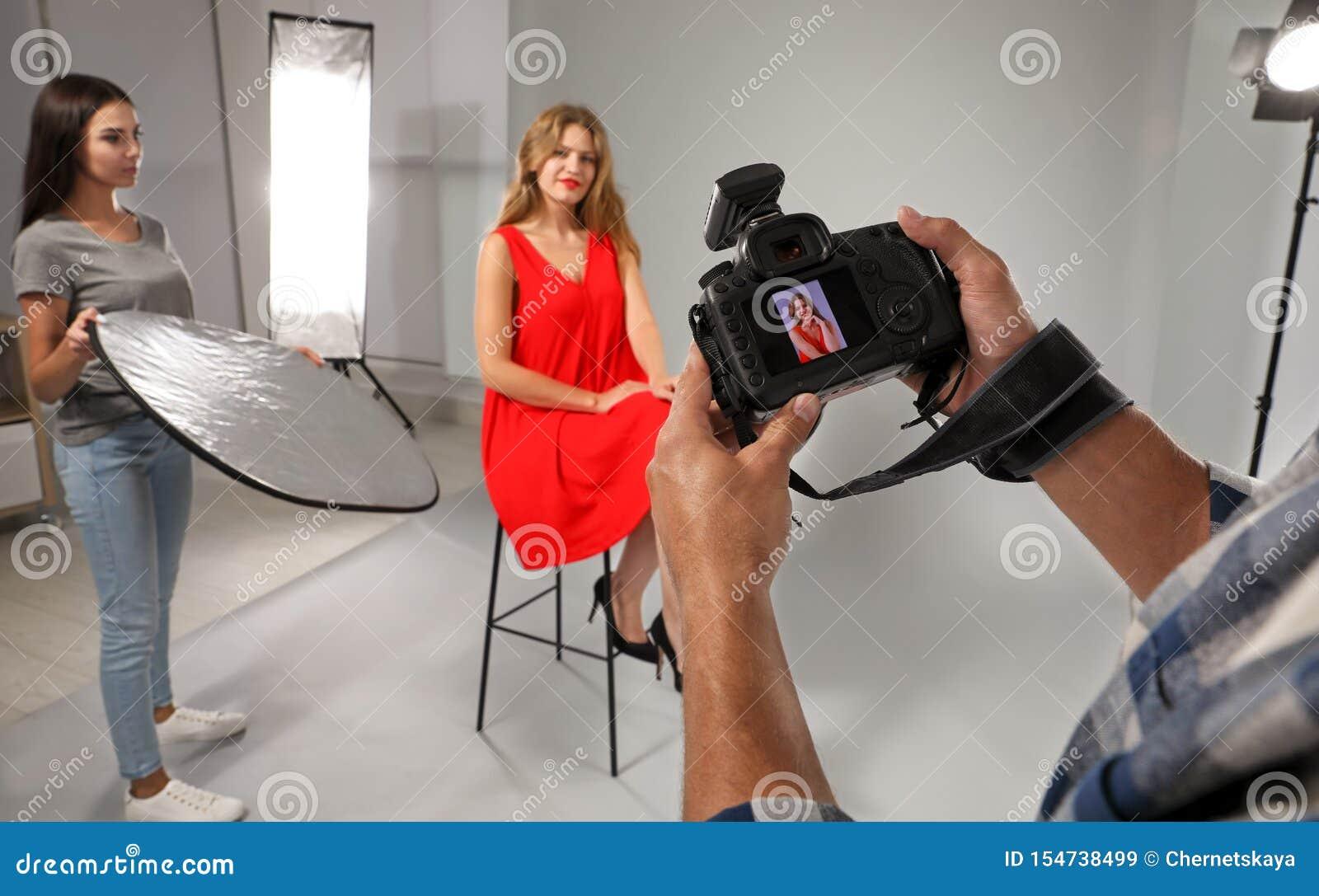 Professioneel fotograaf het herzien beeld op camera en model met medewerker